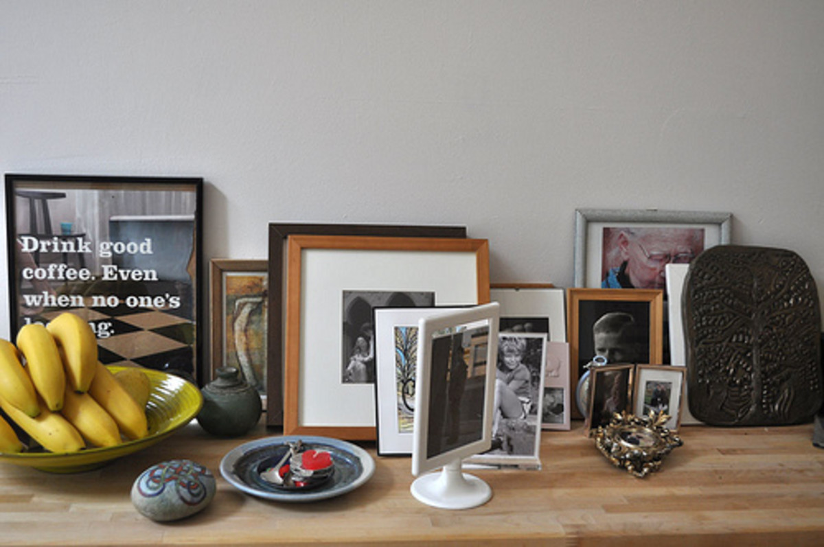A clutter of picture frames on a table make it difficult to focus on a single image.