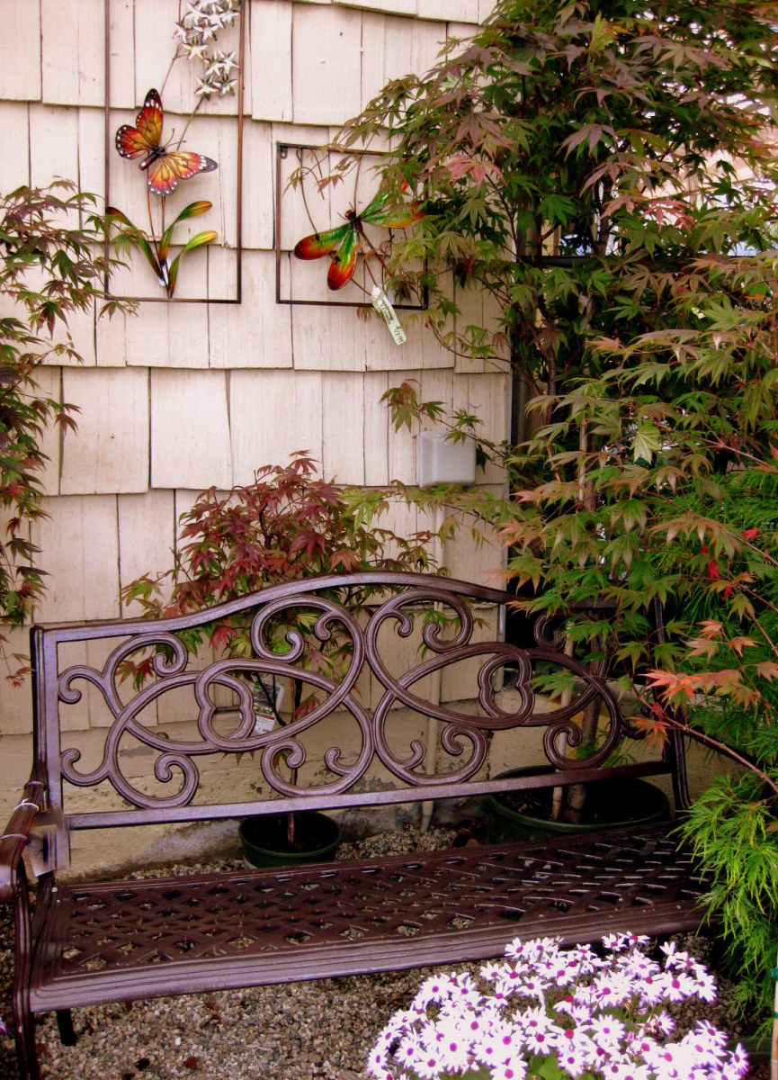 A single bench, potted plants, and some wall art can transform the back of a shed or garage.
