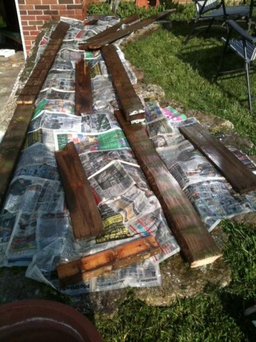 Newspaper and wood kept wet for the duration of time it takes to kill off the grass.