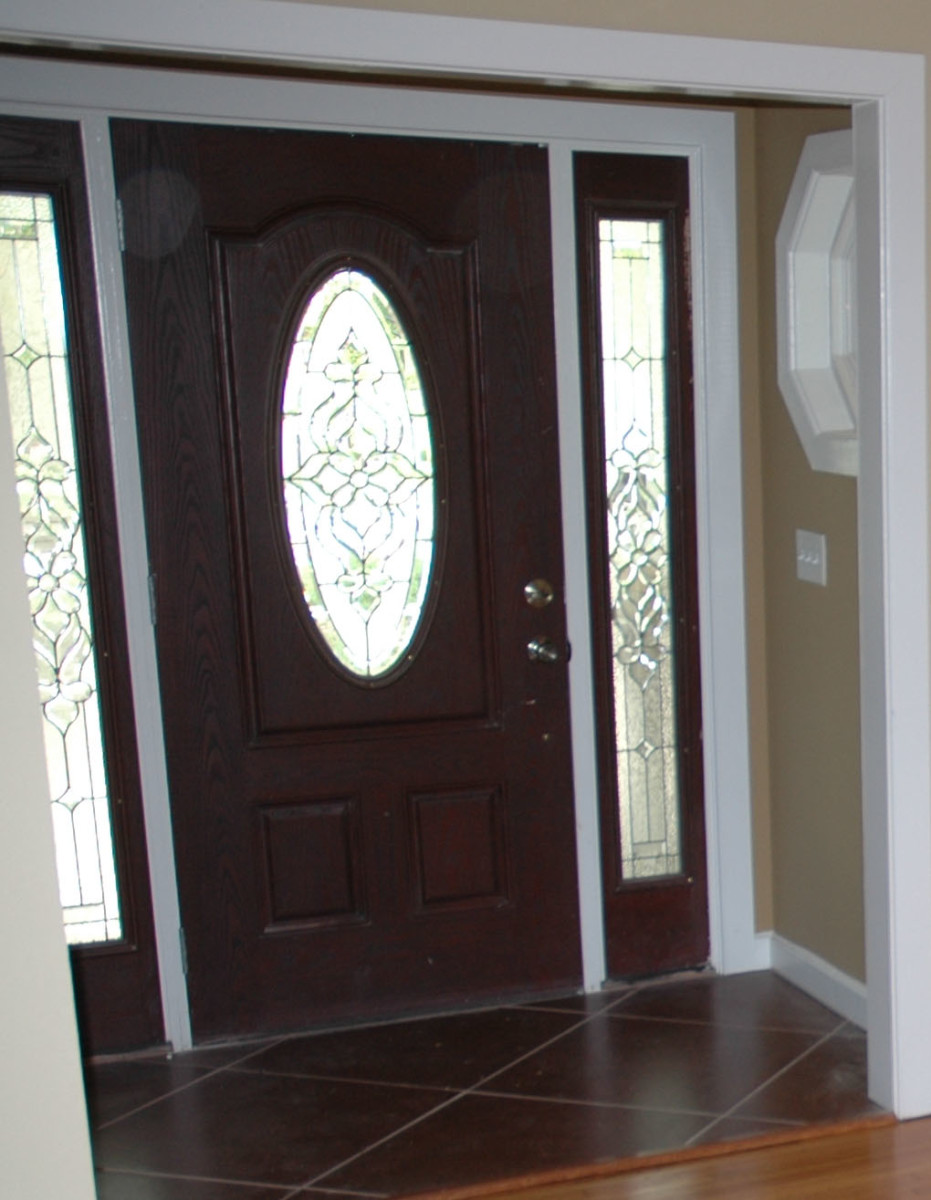 "The decorative glass in the door and side lites add interest and a bit of privacy without blocking light. Ornate beveled glass create a ""picture"" in the door as well as the side lights."