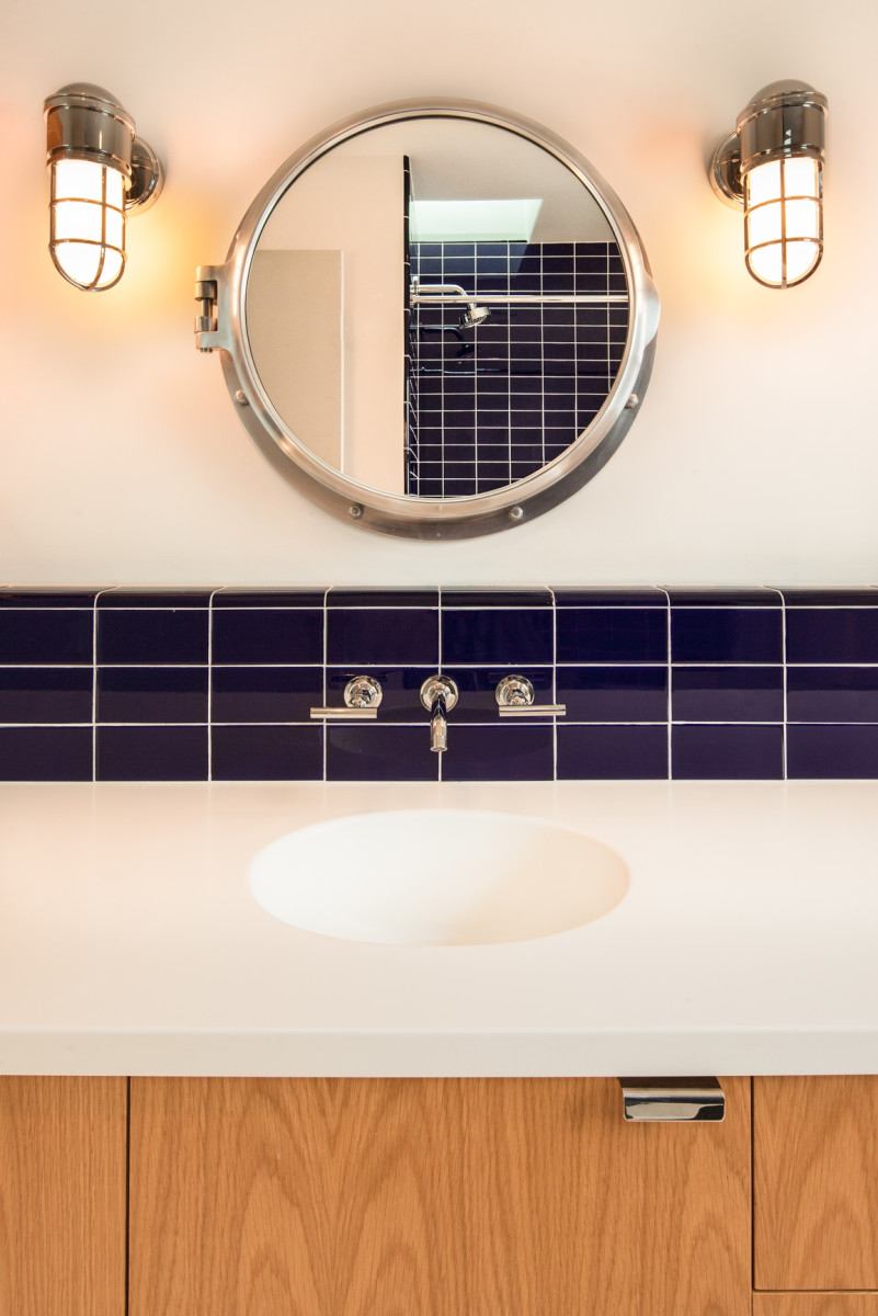 This porthole-shaped mirror gives the bathroom a nautical feel. Its circular shape accentuates the circles in its vicinity.