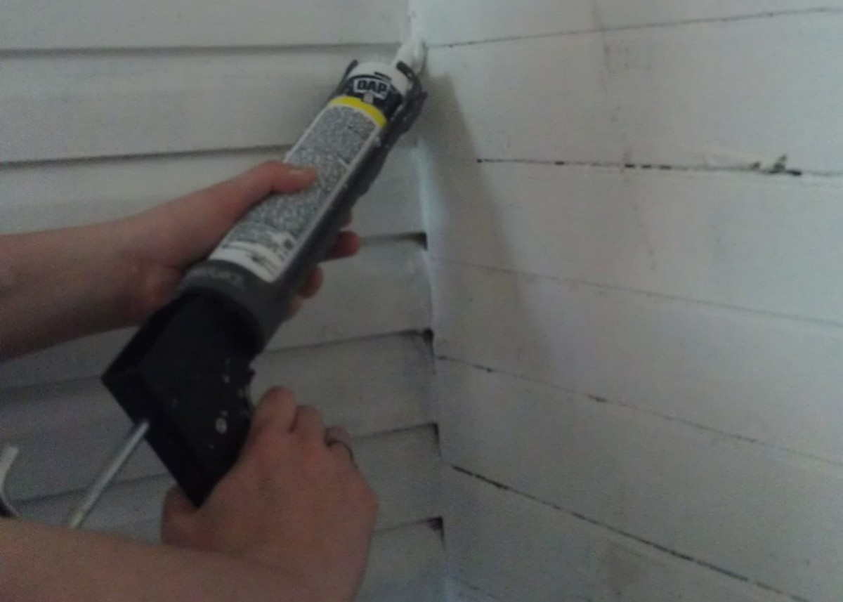 Example showing how to caulk in corners while sealing a home.