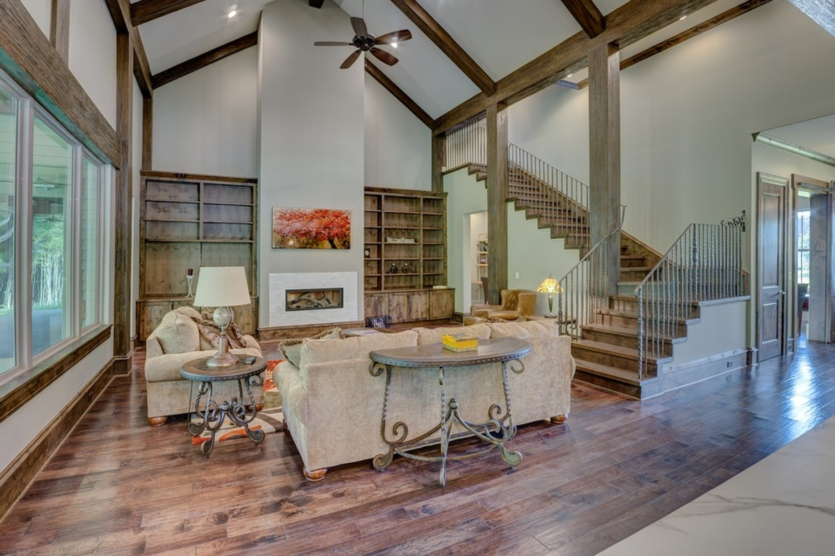 Tall bookcases, ceiling beams and a large fireplace improve the scale of this room.