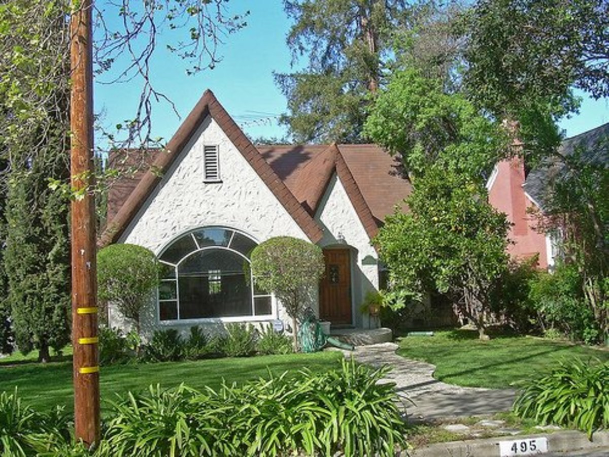 This Tudor bungalow features stucco siding and arched windows.