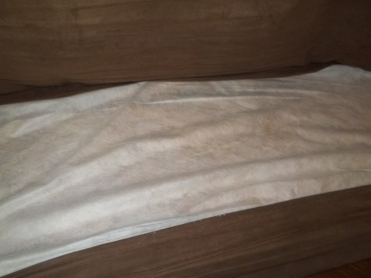 Plywood underneath slipcover or other material to prevent snags on couch and cushions.
