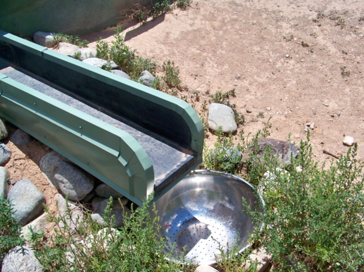 Rainwater Capture - The bowl you see here is a sieve leading to a silt filter pipe that descends to a buried cistern. All Earthship roofs are curved to direct rainwater toward the sieves and their cisterns.