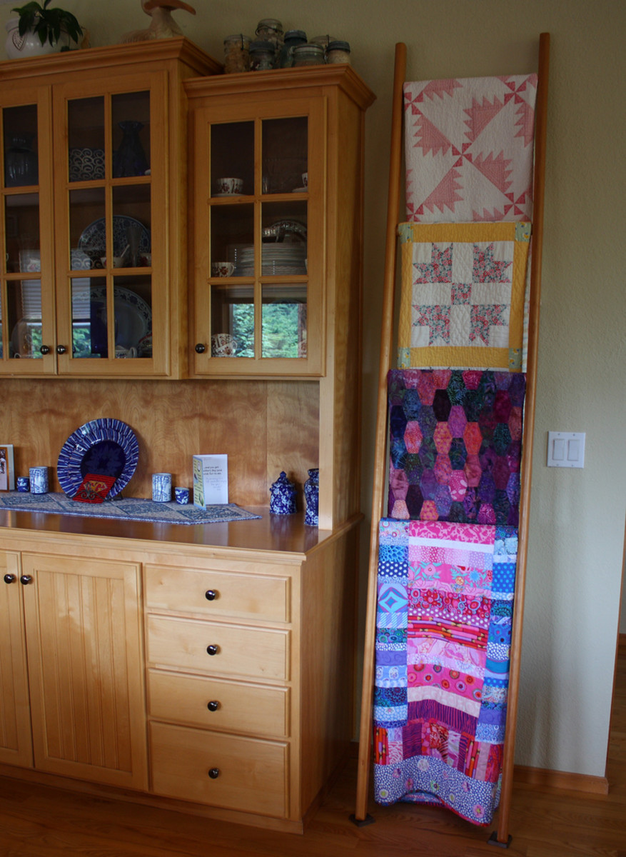 A table runner protects the furniture, and the quilts on the ladder display decorate the dining room while they wait to be called to use.