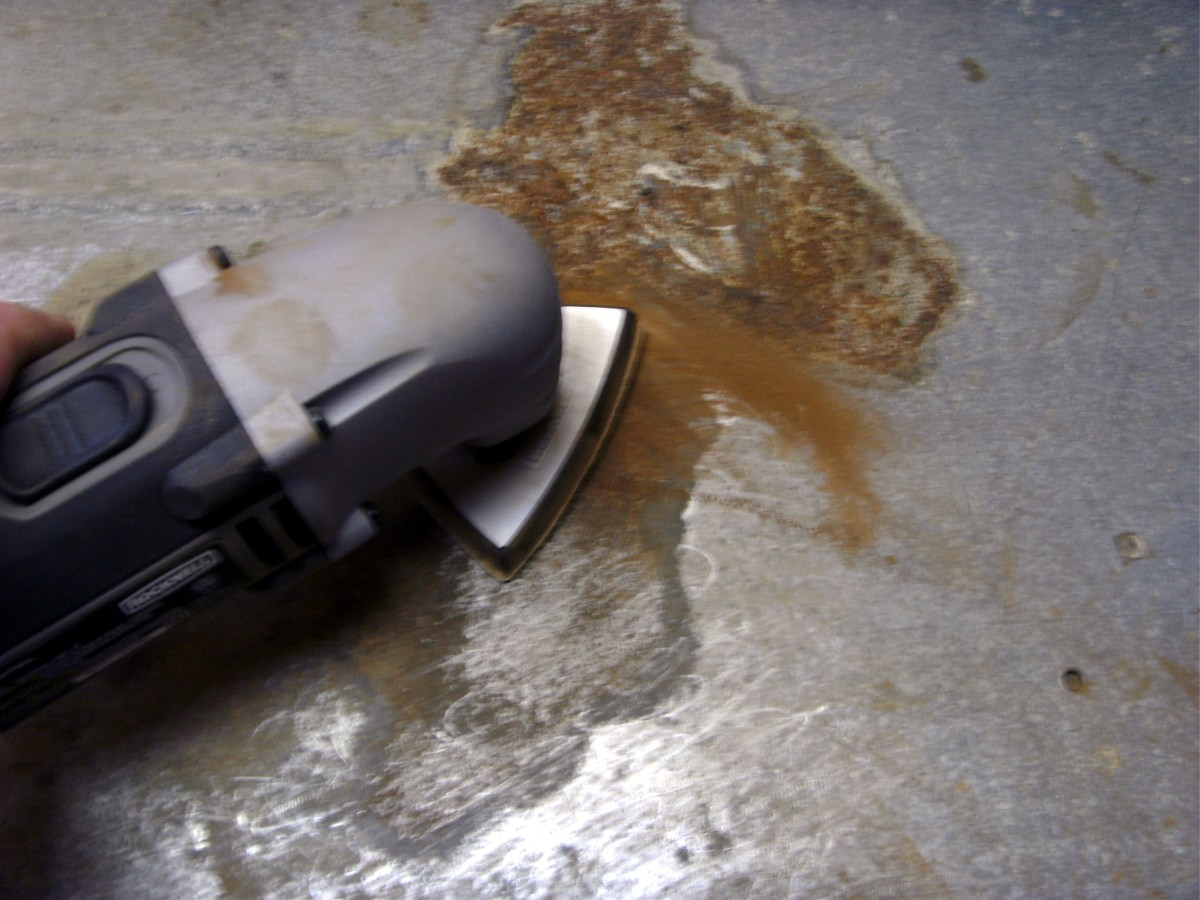 Sanding the rusted surface of a metal workbench.