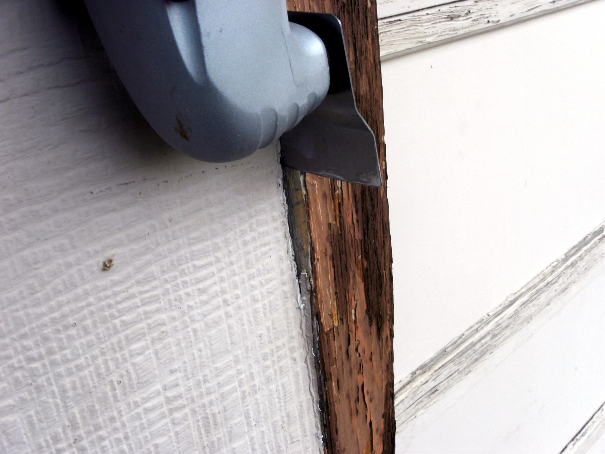 Removing old caulking from an exterior door jamb.