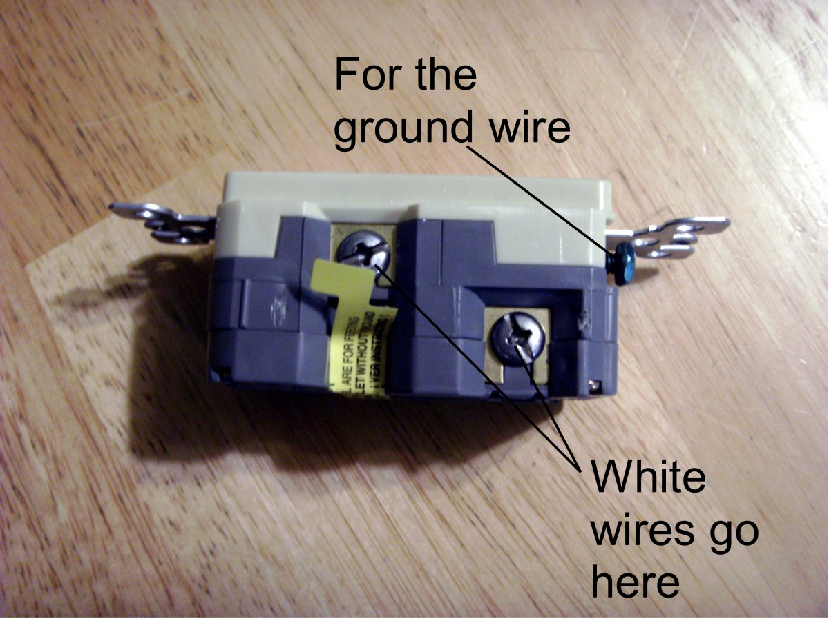 Connections for the neutral (white) wire and ground.  Load wires go behind the tape.