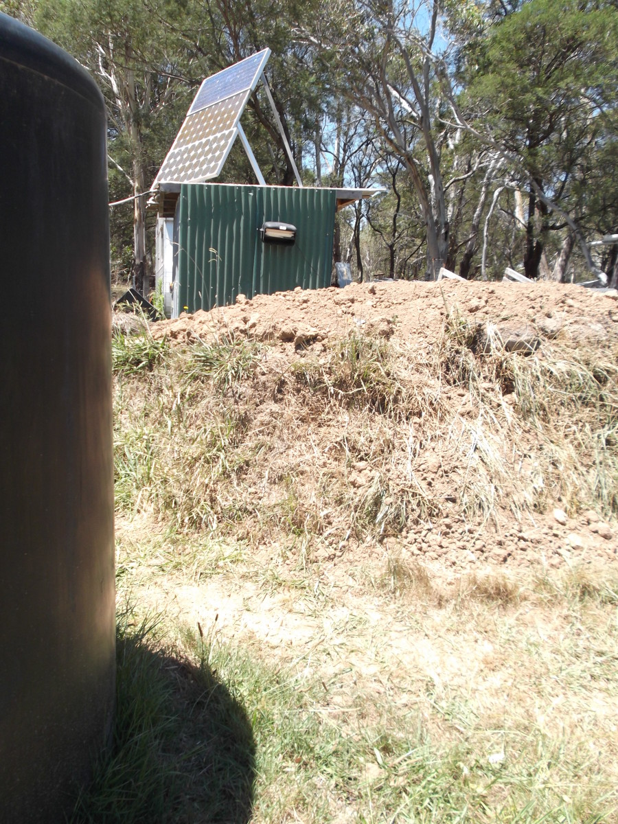 In the foreground is a large black watertank. Between the fire bunker and the bush beyond is the storage area for our solar power system and deep cell batteries. The grass on the bunker was dried to a crisp by high temperatures and fierce dry winds.