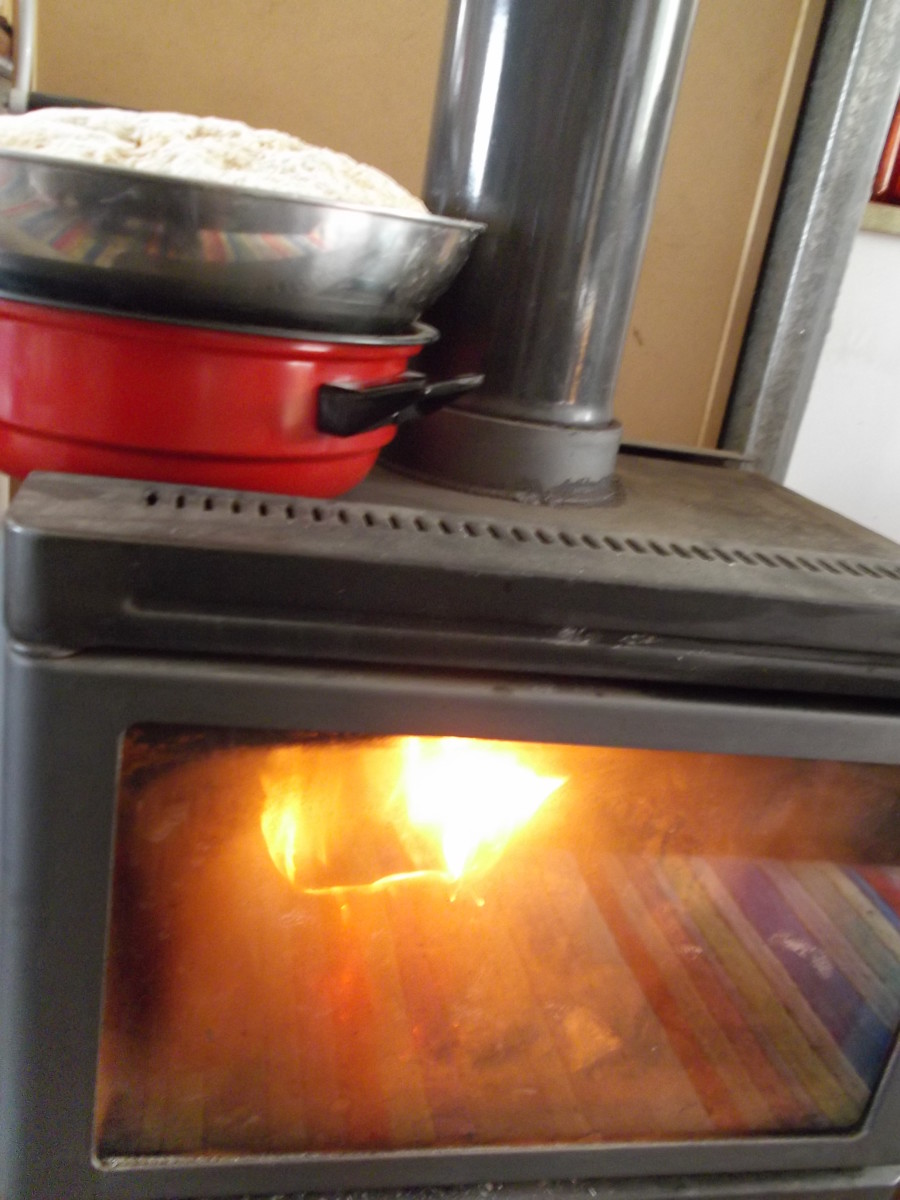 This basic slow combustion heater is put to work helping dough rise. The bowl is elevated from direct heat. This also works as dual-purpose heating.