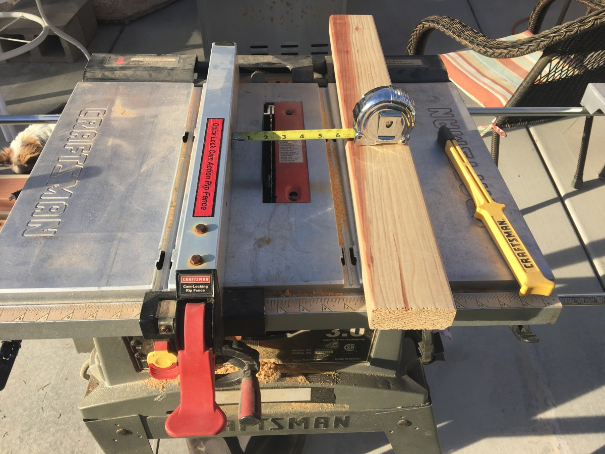 Setting up a fence on the table saw for a width of just over 2 inches.