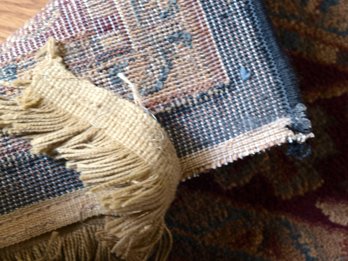Torn rug fringe on the back side of the rug.