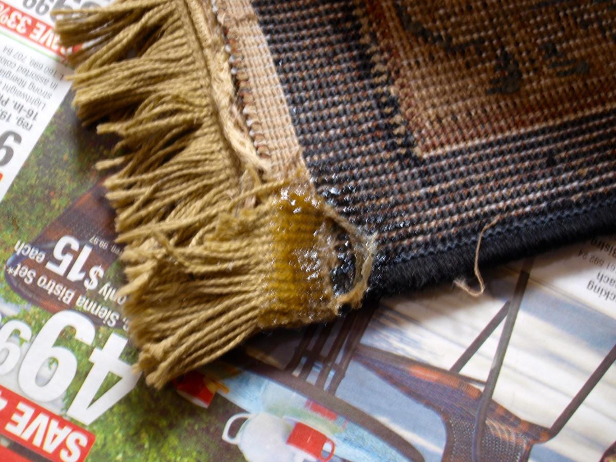Rug fringe glued down.