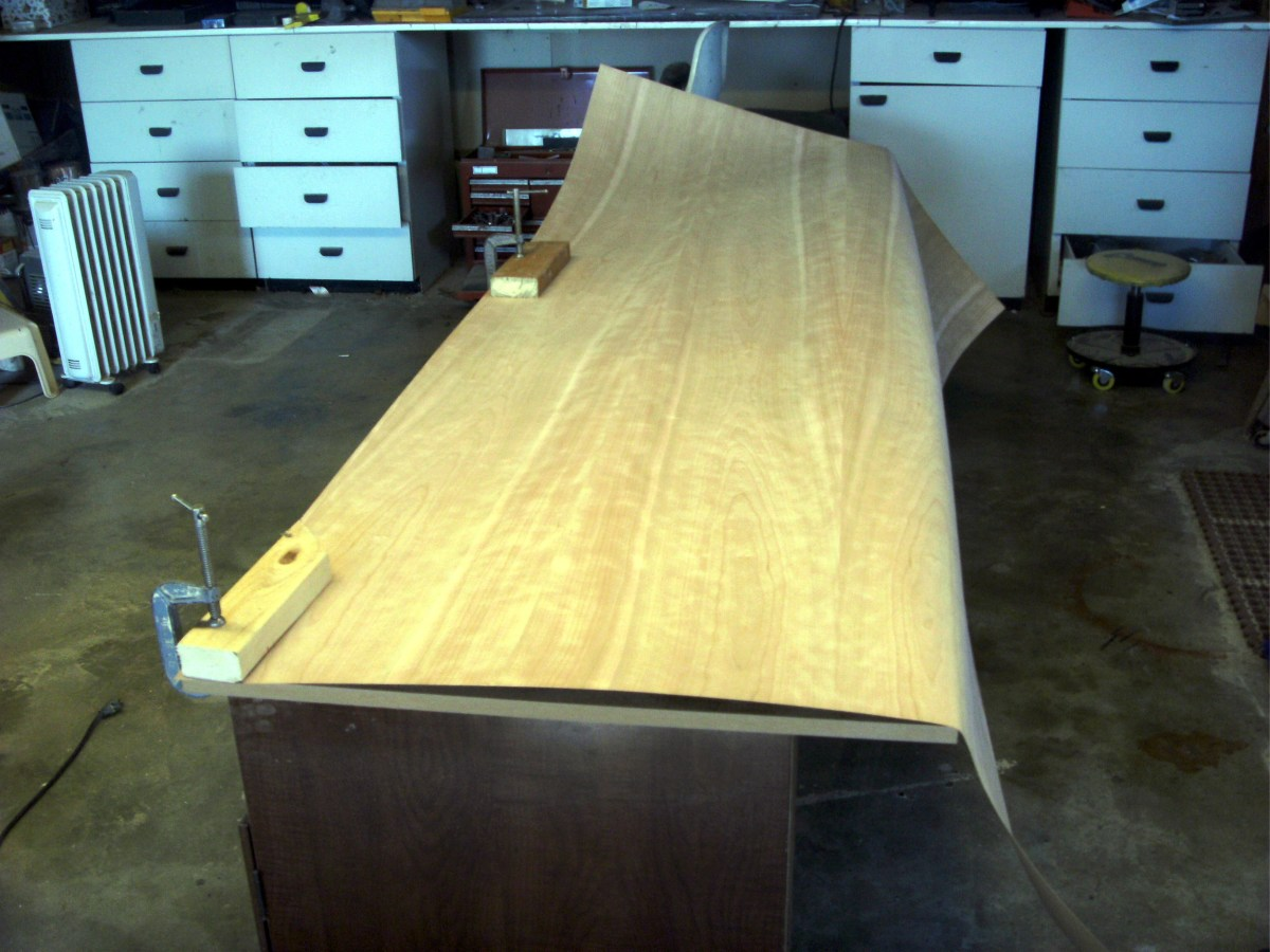 The veneer is clamped to the desktop to mark for cutting