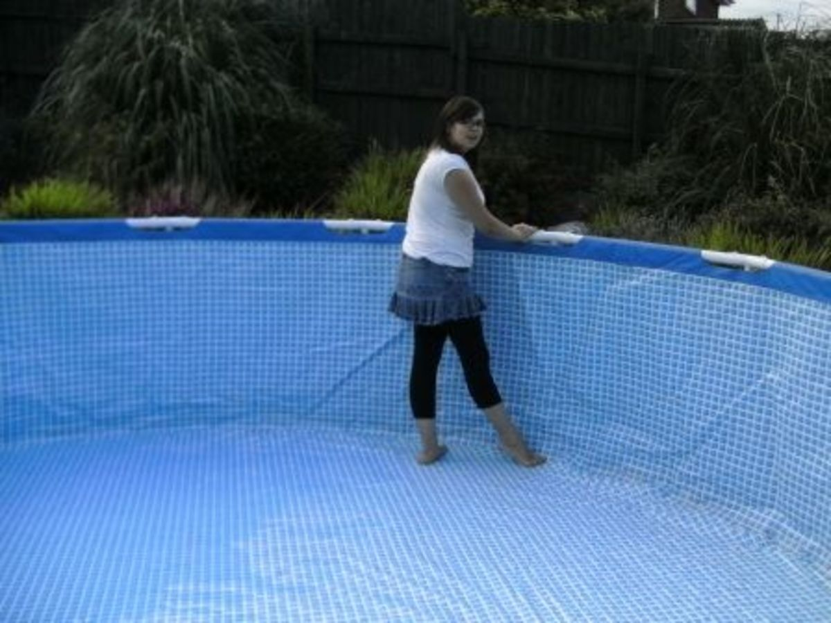 Erecting the pool, pushing out the creases before filling with water