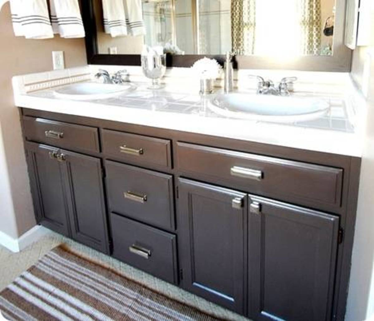 Kate updated her old vanity with a rich espresso finish and added chrome hardware.  Notice the counter top is still the same yet it looks like a completely new vanity.