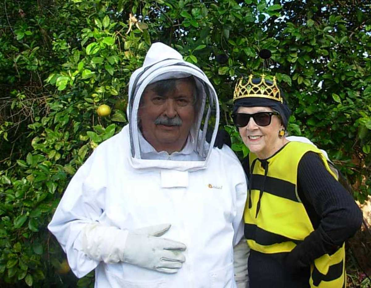 Jim Arnold is dressed in a beekeeping suit and Linda Fessel is dressed as his Queen Bee for Halloween.