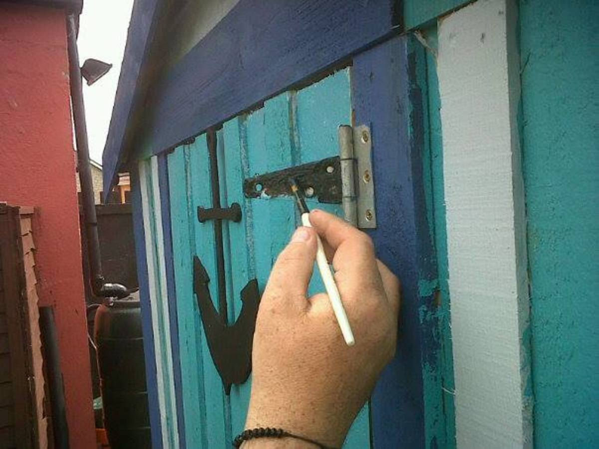Painting the hinges on the garden shed