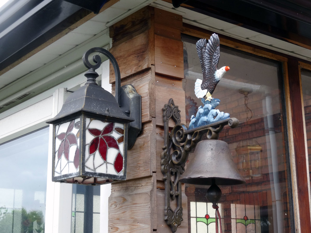 Lamp and Bell on corner of conservatory adorning decking.