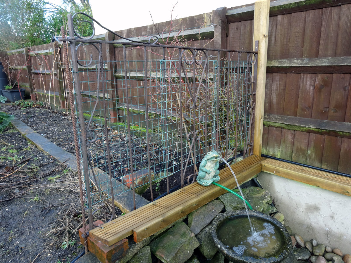 Our old garden gate repurposed as an anti-fox fence above pond.