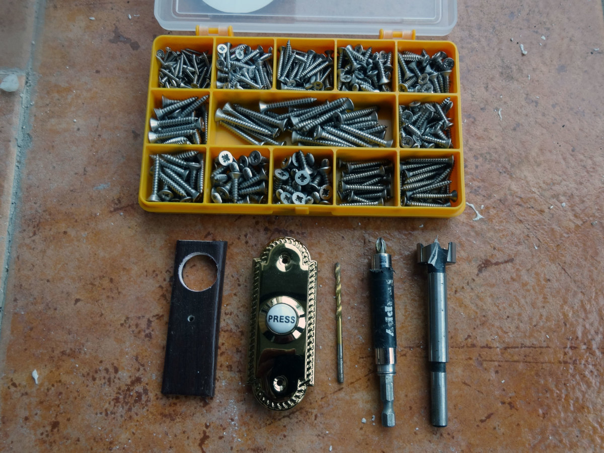 Push bell, drill bits and self-tapping screws used to fix the doorbell in place.