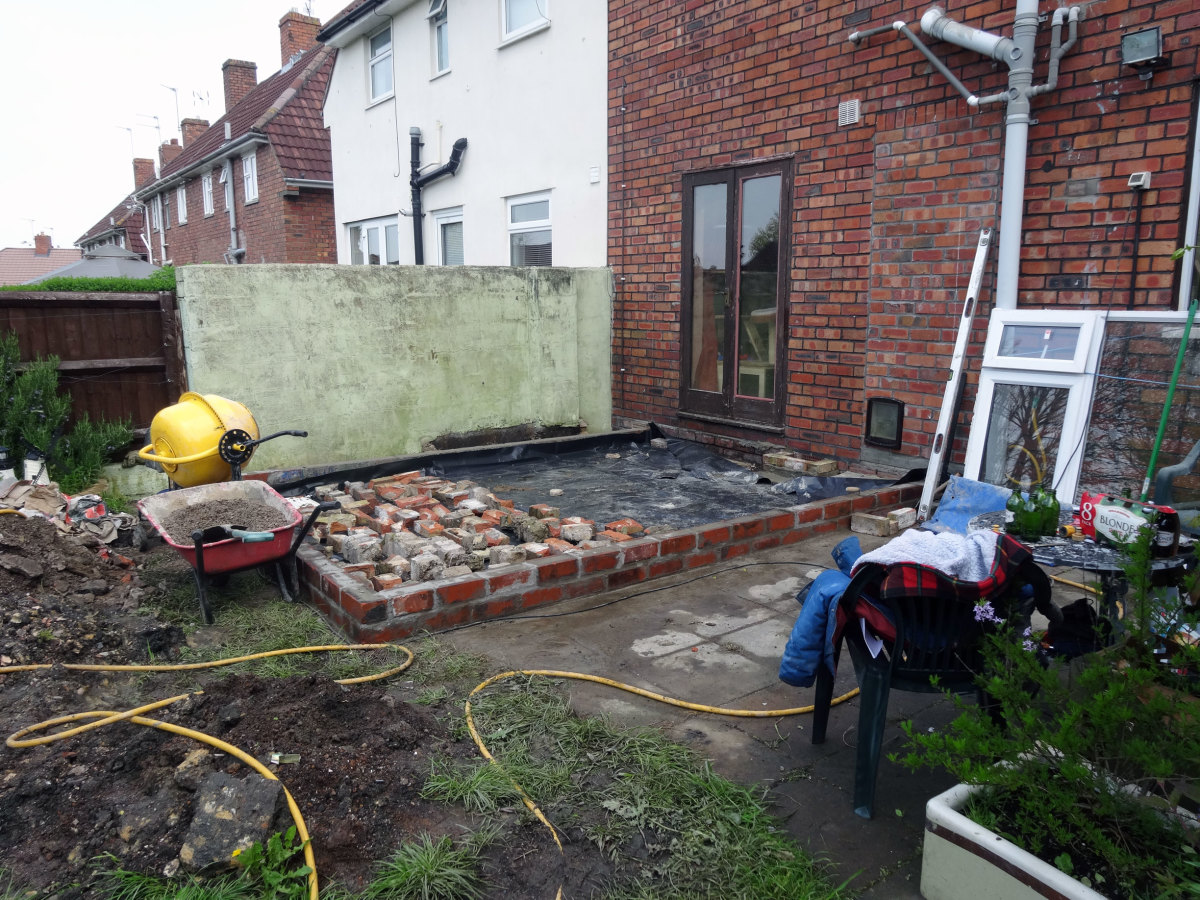 Foundation wall built, damp proof membrane laid over hard-core.