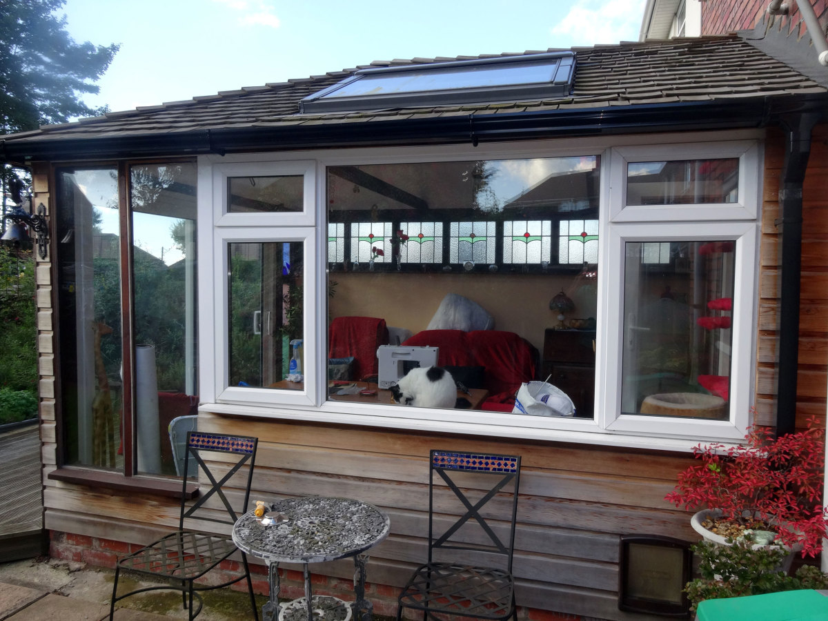 Timber frame cedar wood clad conservatory with cedar wood roof tiles.