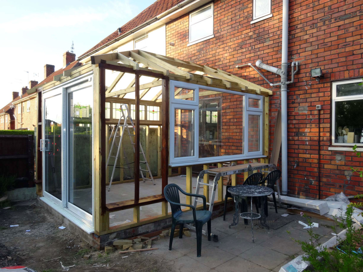 Fitting the windows and patio doors to the timber frame.