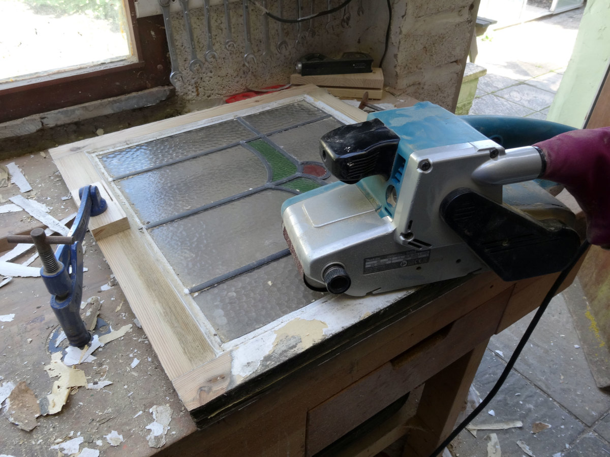 Using a belt sander to clean take the window frames back to the bare wood.