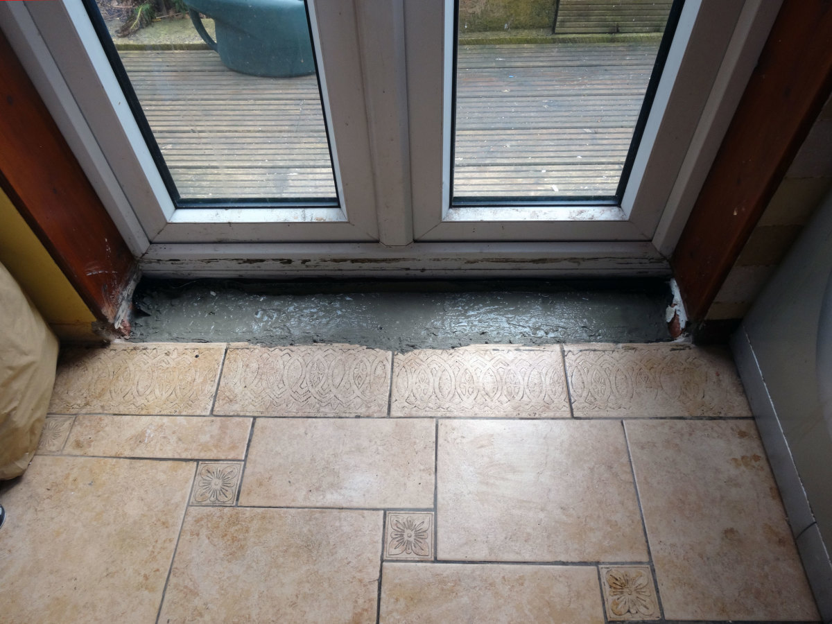 Gap filled with concrete to an inch below floor level; to allow for tiling.