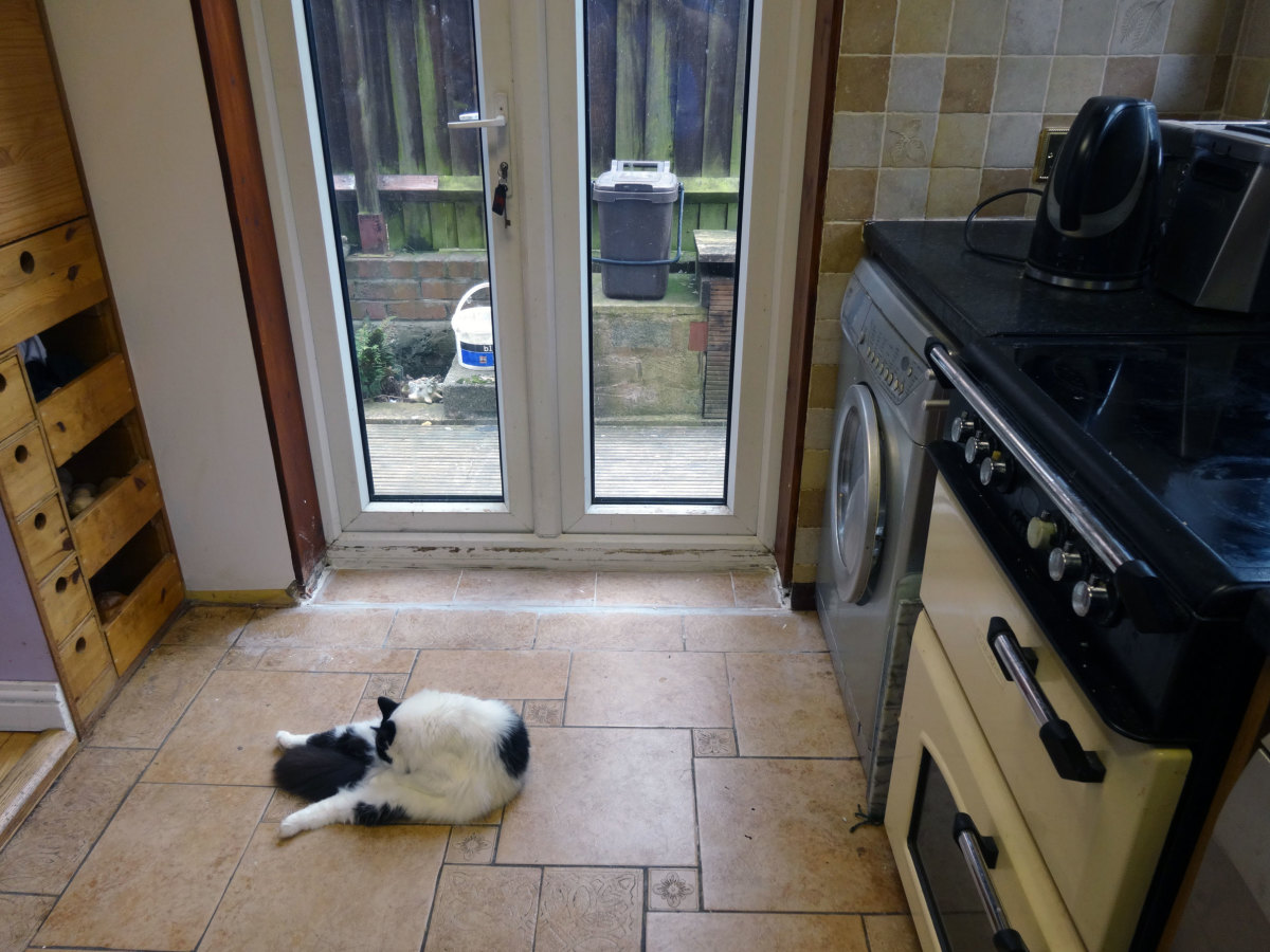 Floor in front of backdoor tiled with tiles recycled from the old doorstep.
