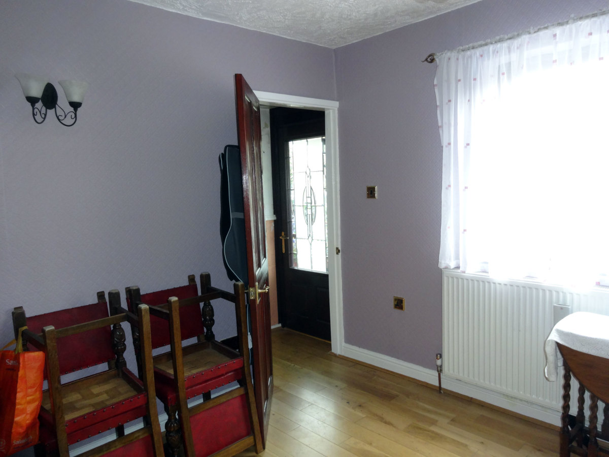 Room decorated; dining room door open, with internal porch door in view.