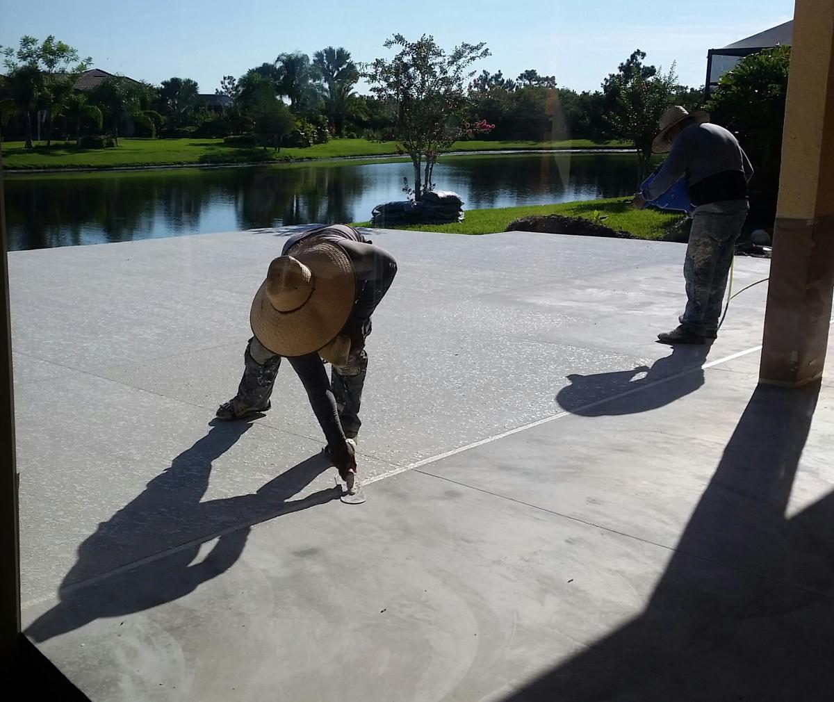 The upright worker has a hopper filled with the CoolDeck solution and he's spraying it on the concrete. The worker who's leaning down has a trowel to spread and flatten it. He's wearing spikes strapped on his shoes to avoid treading on the wet glop.