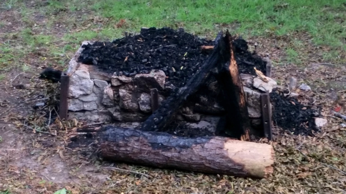 This stone-and-block fireplace may not be pretty, but it does elevate fuel away from the soil.  And the charred logs show that there was lots of water to extinguish the fire when needed.
