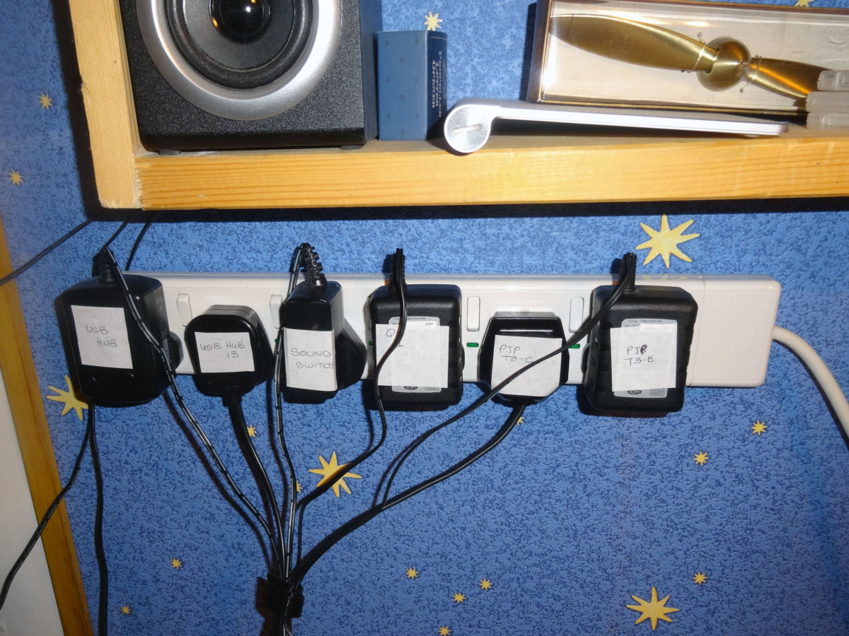 One of the three 6-gang (individually switched) 13Amp wall mounted extension sockets above the desk populated with plugs.