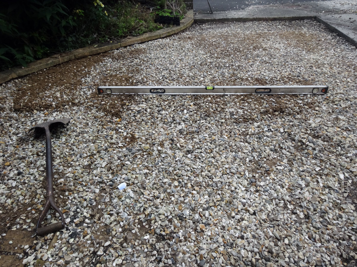 Using spirit level and shovel to level the gravel.
