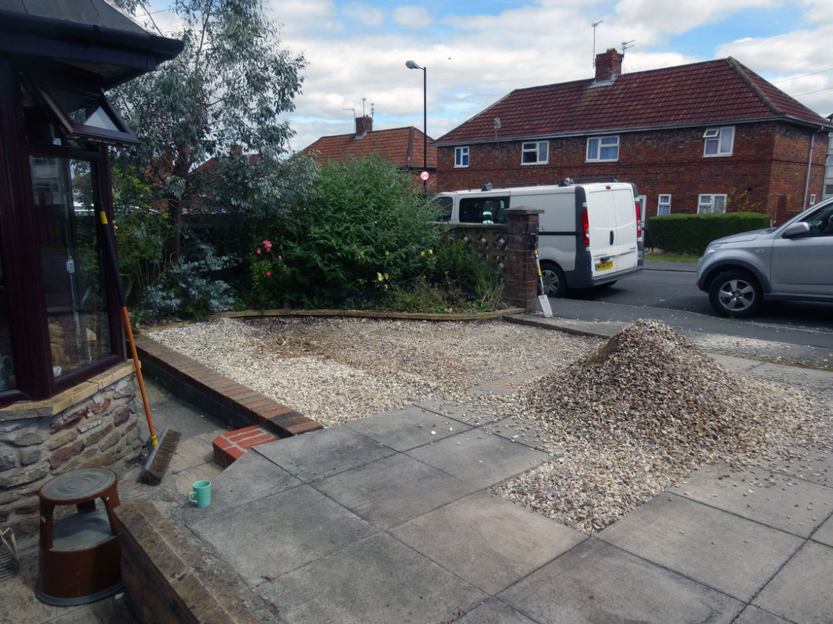 Lowering existing gravel drive by 2 inches to the required depth for laying the plastic grids.