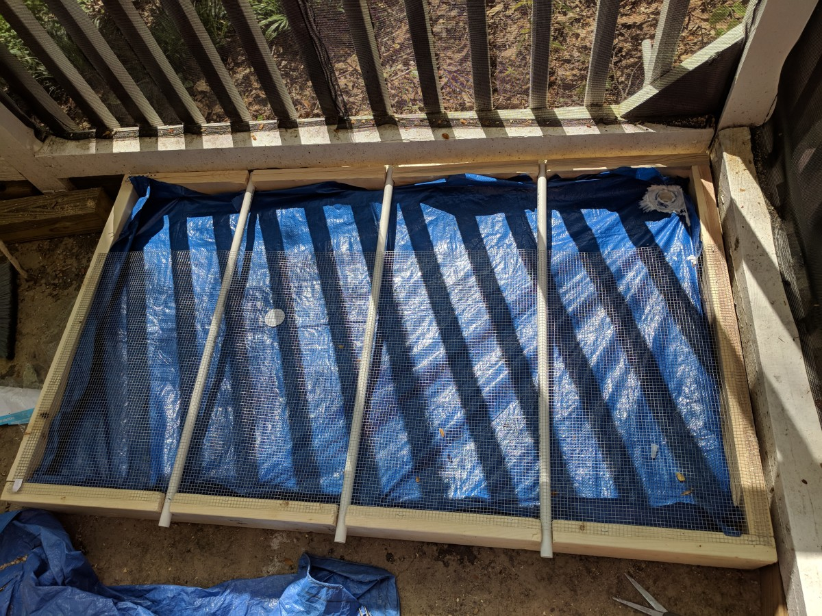 I forgot to take a picture before I started putting the hardware cloth and PVC pipe inserts -- but look past that and you'll see my tarp. I recommend a shower curtain instead. staple the shower curtain in to keep liquids off the plywood,