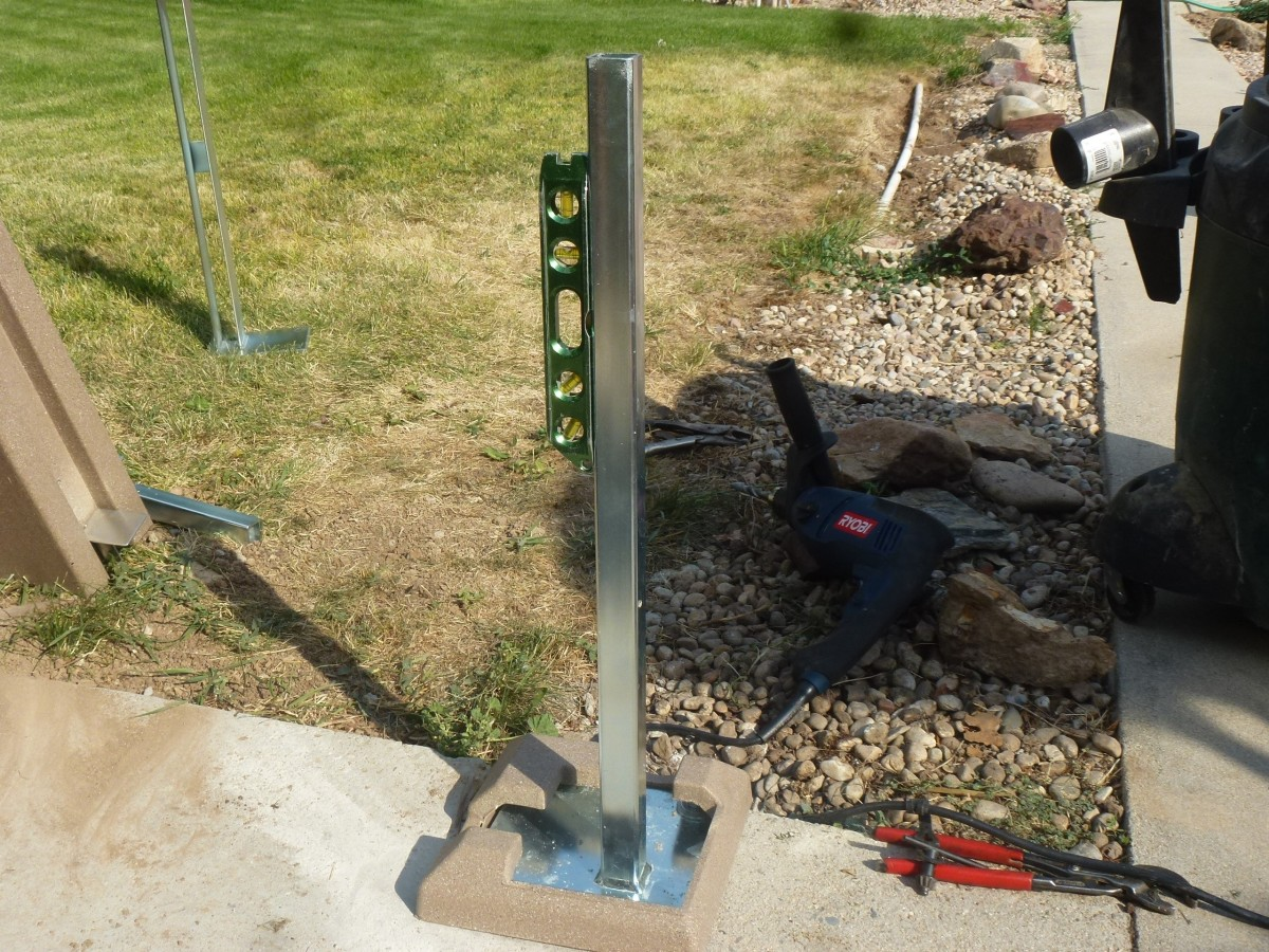 Leveling the bracket.  The post will slide over the upright steel, and it must be plumb.  Washers may be added under the steel plate to plumb it vertical. The trim piece has been temporarily set into place to verify post location.