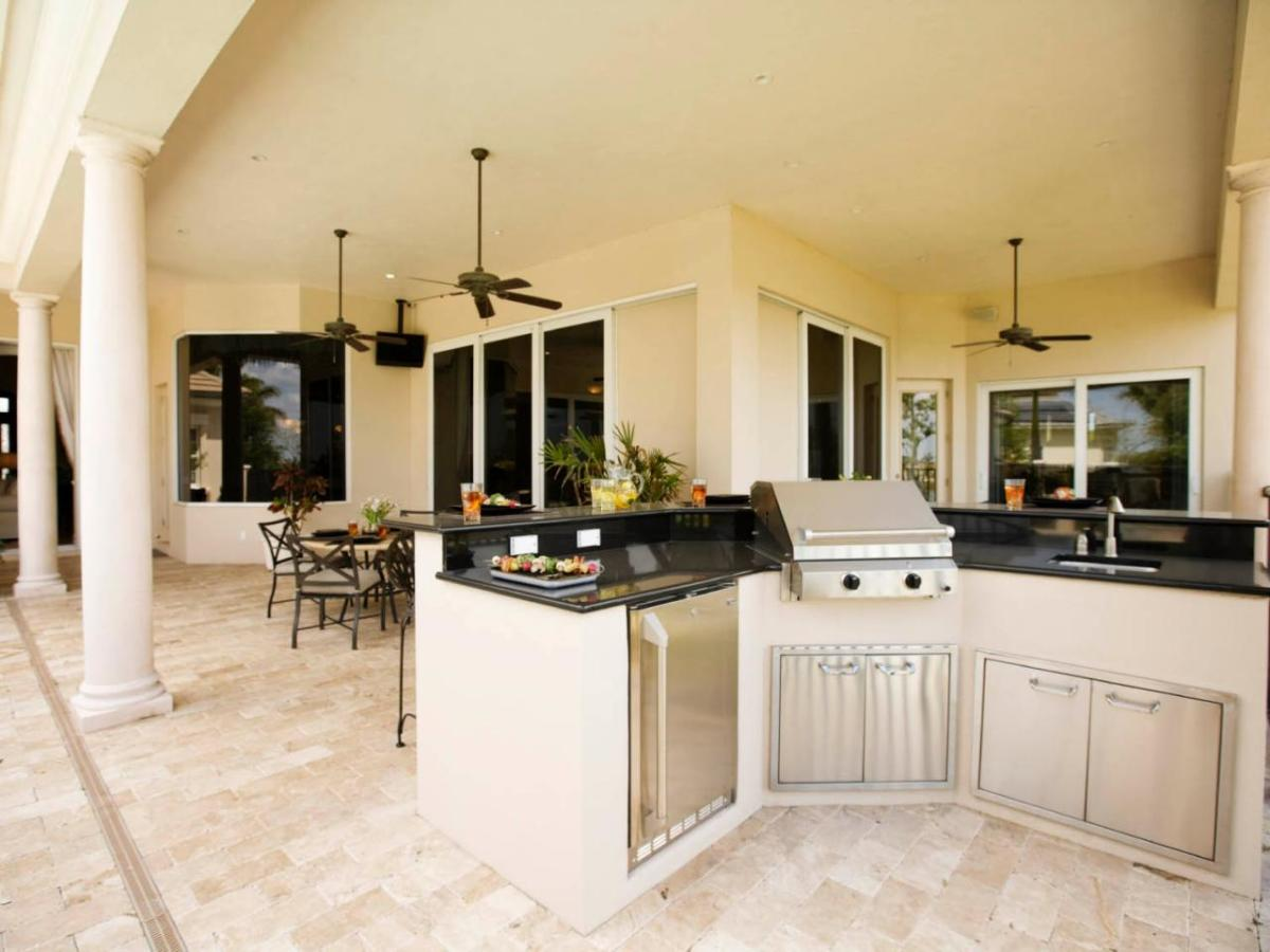 This traditional outdoor kitchen and dining space is easily accessible to the indoor kitchen.