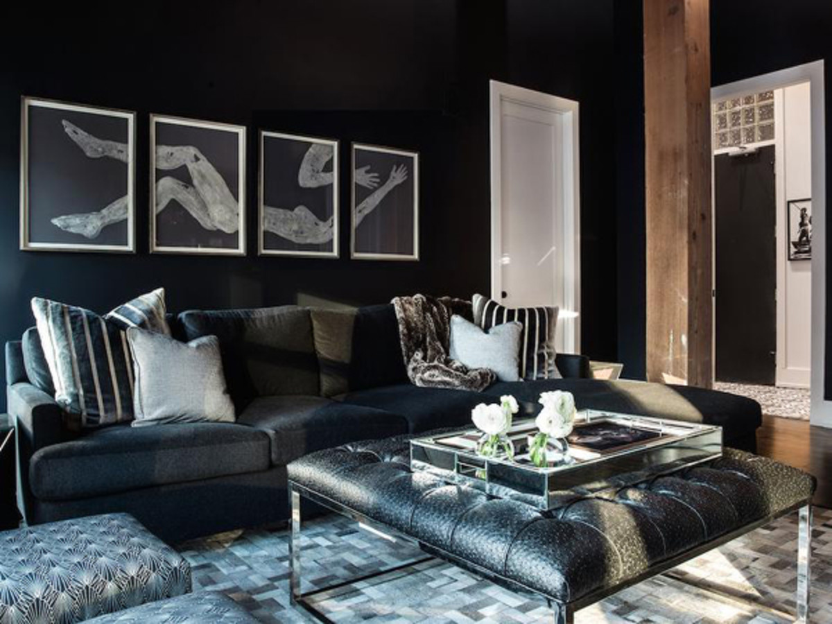 Black walls and furnishings create a stylish cocoon-like environment.