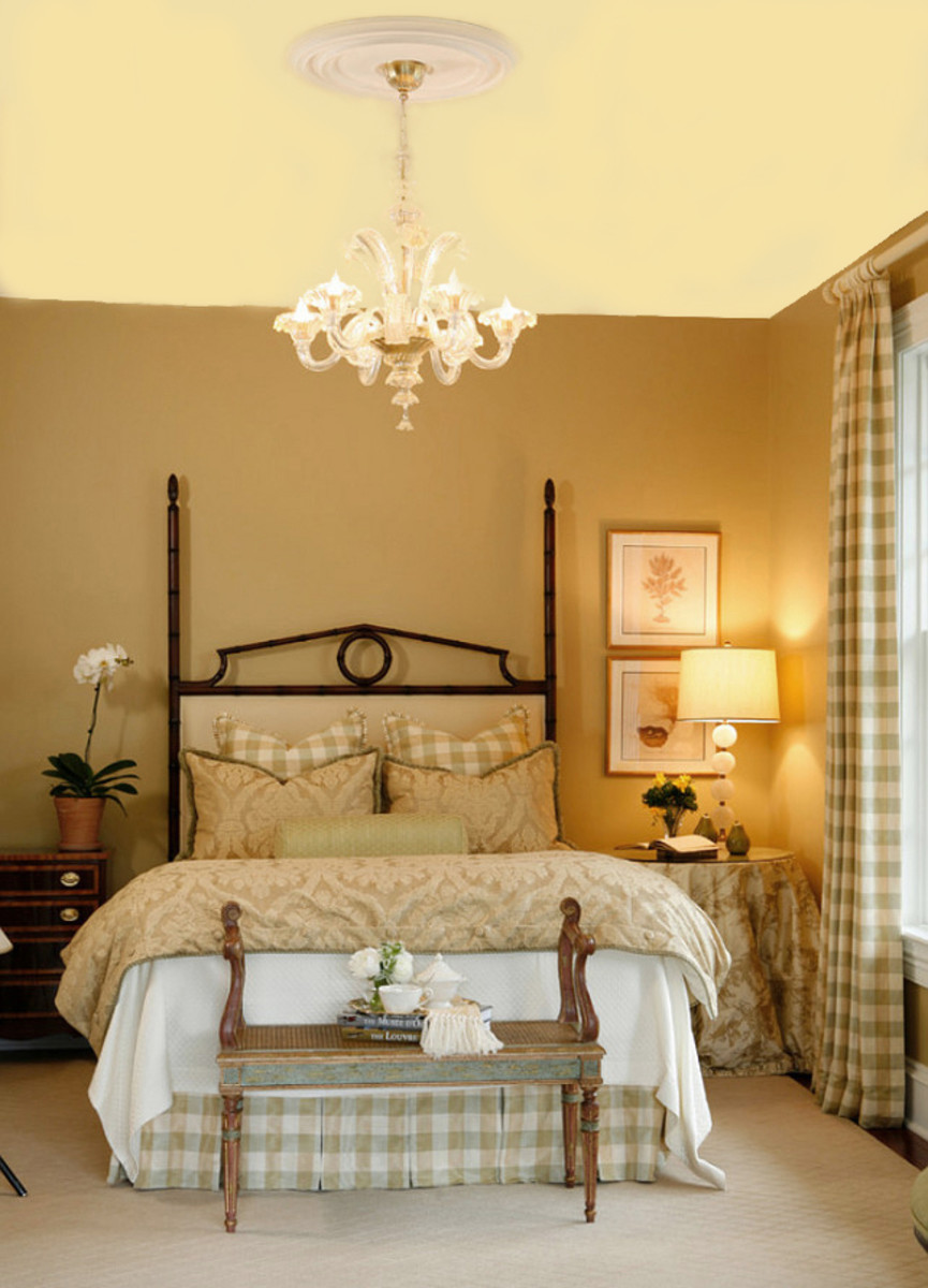 Warm walls and a butter yellow ceiling give the bedroom a spacious feel.