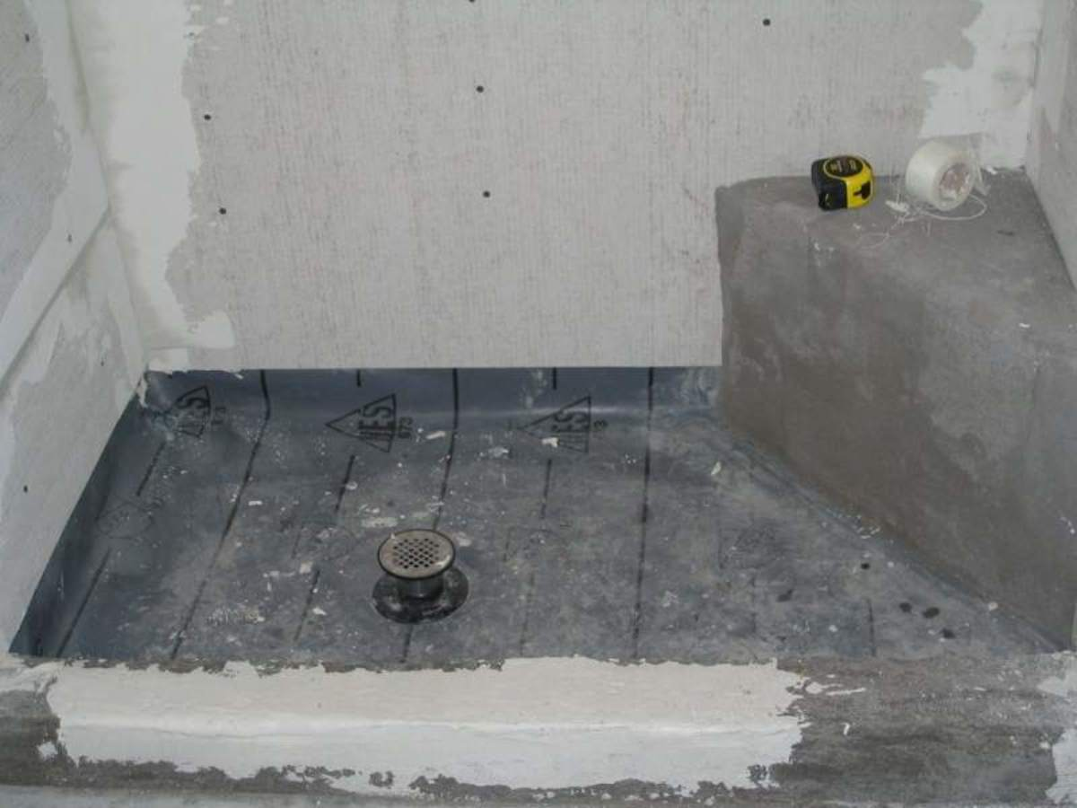 Notice the wall boards do not extend down to the bottom of the shower membrane.