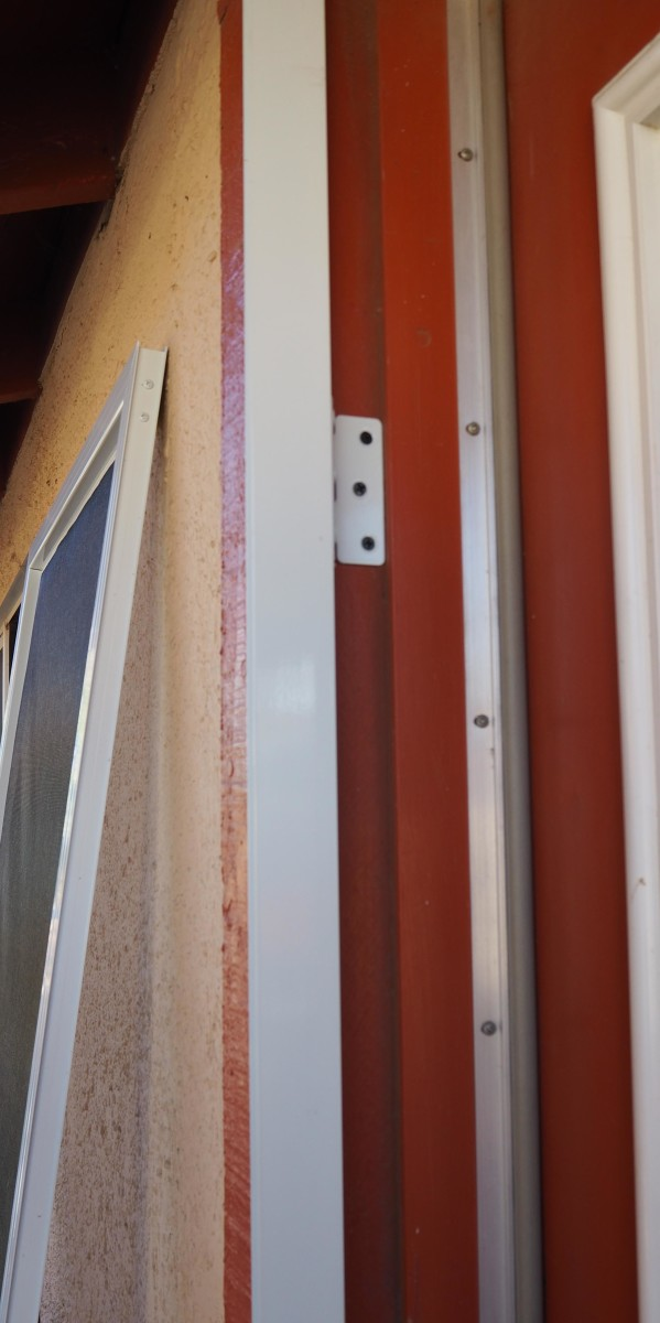 Once the hinge panel is fully installed, the screen door slides back into the channel, and gets screwed in place