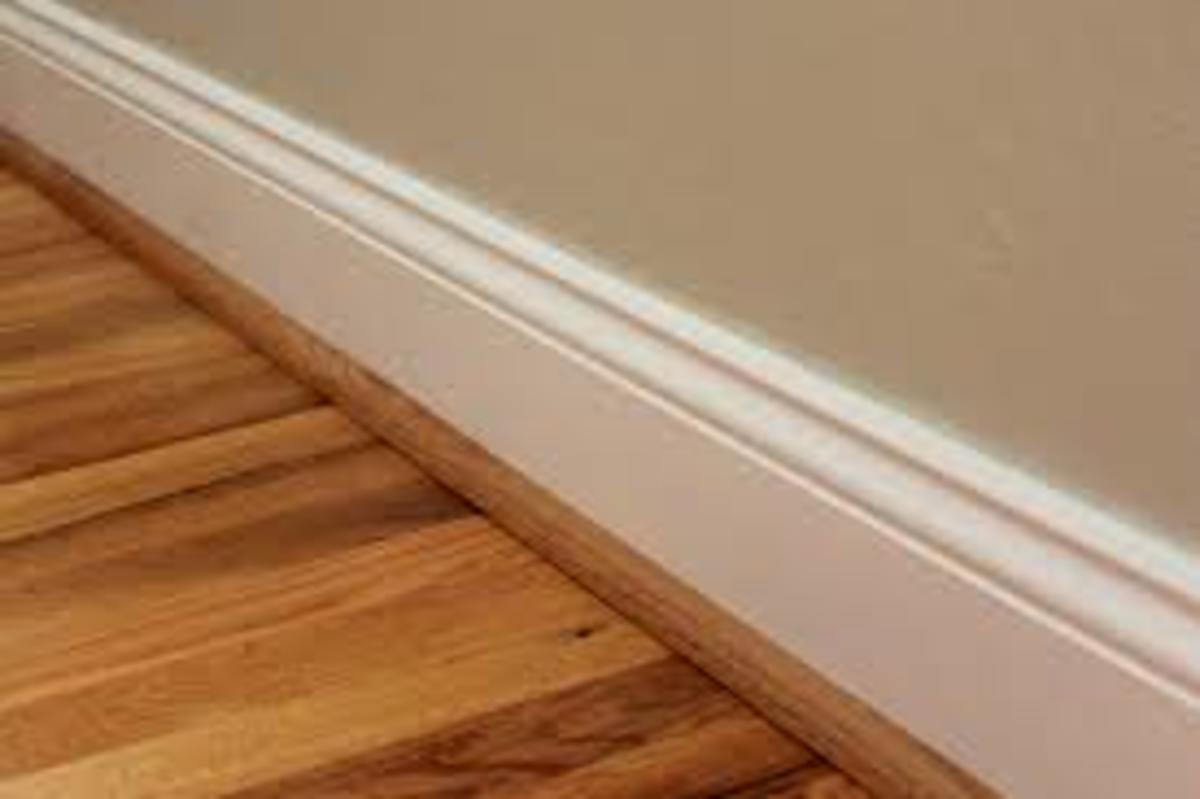 See that strip that covers the gap between the baseboard and the floor? That's what we call quarter round trim. Sometimes it's painted, but sometimes (as in this photo) it's not.
