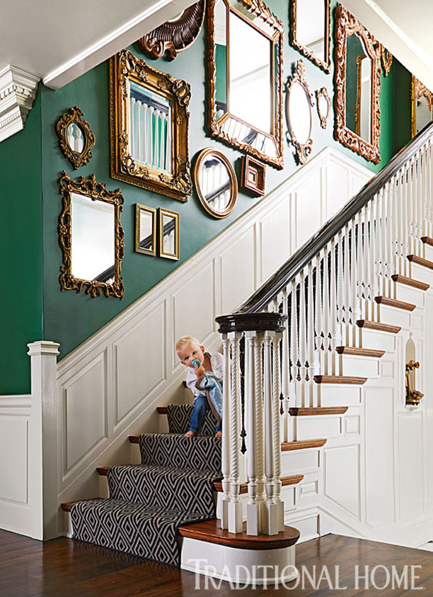 A mirror gallery brightens up the staircase and contrasts against the emerald wall.