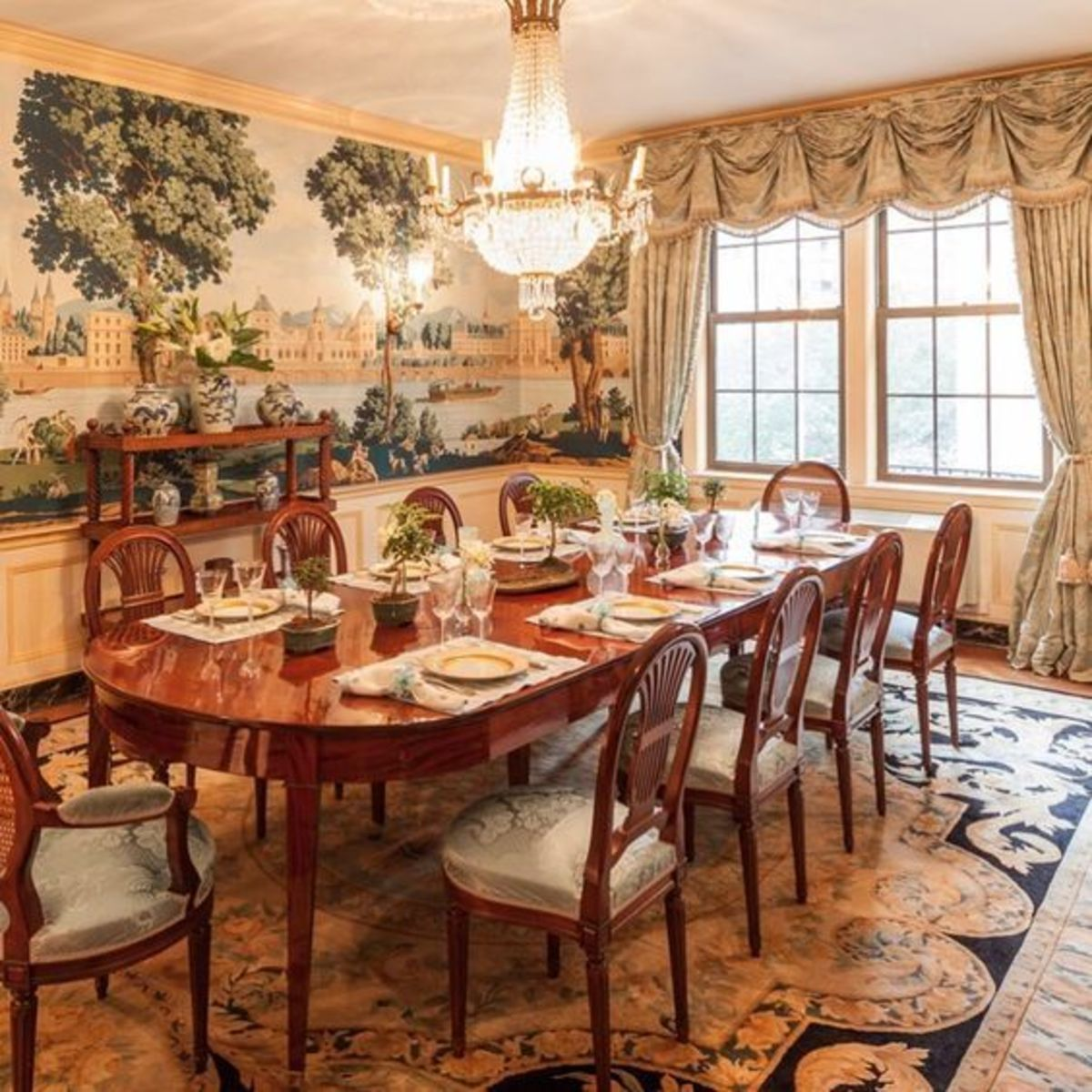 Stunning curtains and an antique Oriental rug gives the dining room a traditional feel.