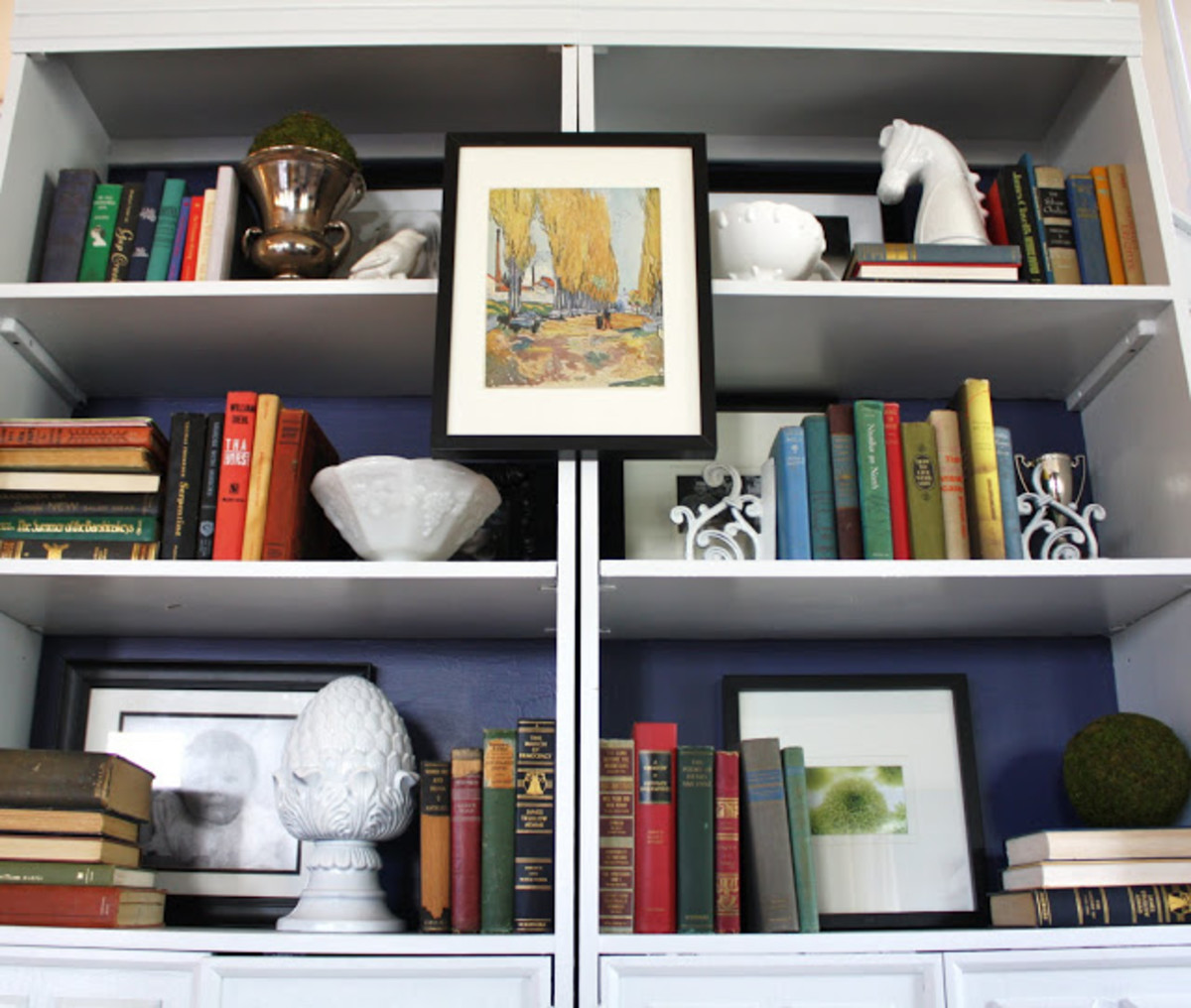 Adding artwork to a bookshelf gives it a fresh look.